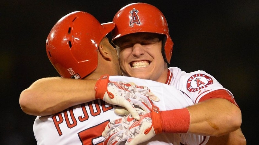 May 13, 2015; Anaheim, CA, USA; Los Angeles Angels center fielder Mike Trout (27) hugs first baseman Albert Pujols (5) after Pujols hit a game winning sacrifice fly ball in the eleventh inning of the game against the Colorado Rockies at Angel Stadium of Anaheim. Angels won 2-1. Mandatory Credit: Jayne Kamin-Oncea-USA TODAY Sports