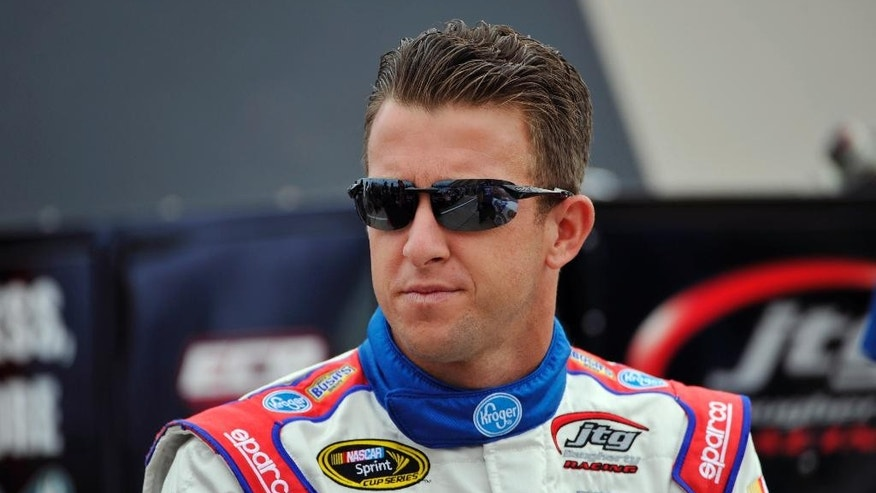 AJ Allmendinger waits by his car before qualifying for Sunday's NASCAR Sprint Cup series auto race at Watkins Glen International, Saturday, Aug. 8, 2015, in Watkins Glen. N.Y. (AP Photo/Derik Hamilton)