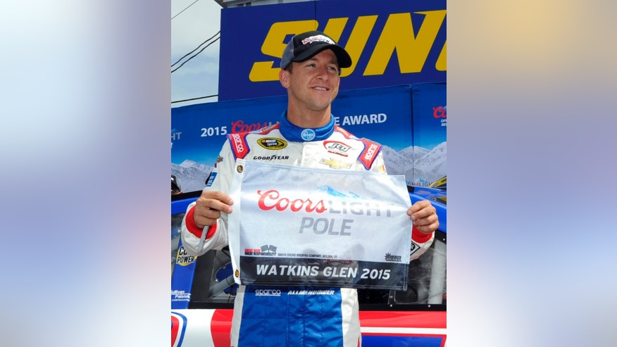 AJ Allmendinger poses with the pole award after qualifying for Sunday's NASCAR Sprint Cup series auto race at Watkins Glen International, Saturday, Aug. 8, 2015, in Watkins Glen. N.Y. (AP Photo/Derik Hamilton)