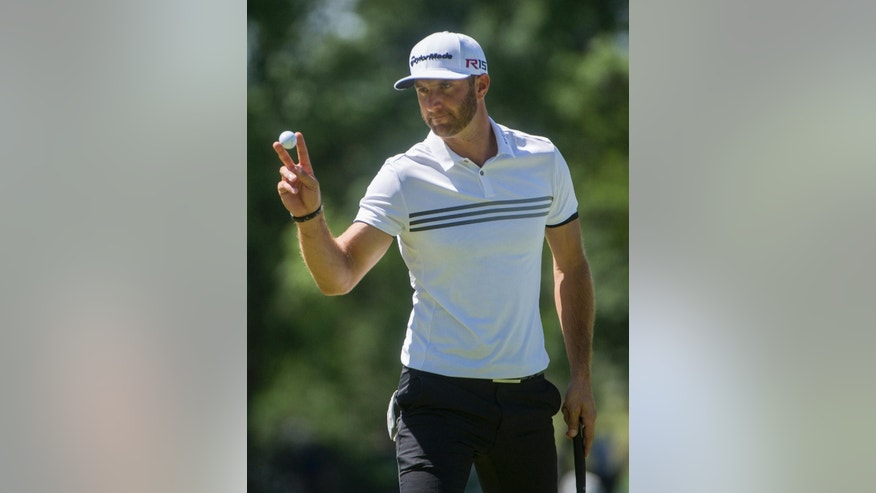 Dustin Johnson reacts after making a par on the second hole during the second round of the Bridgestone Invitational golf tournament in Akron, Ohio, Friday, Aug. 7, 2015. (AP Photo/Phil Long)