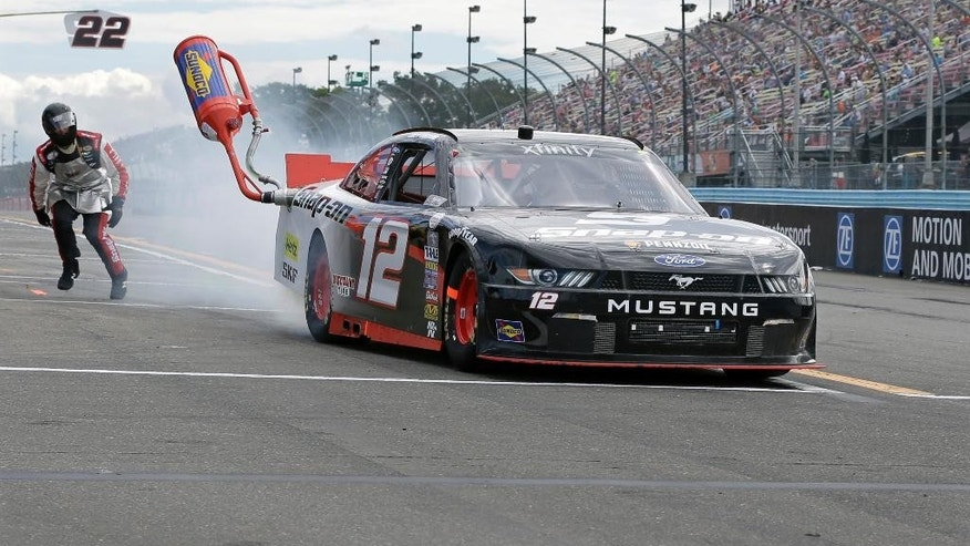The gas man can't catch Joey Logano (12) as he leaves the pits with a gas can stuck during the NASCAR XFINITY series auto race at Watkins Glen International, Saturday, Aug. 8, 2015, in Watkins Glen, N.Y. (AP Photo/Mel Evans)
