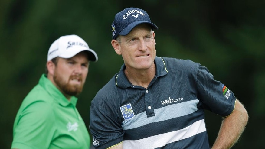 Jim Furyk watches his ball after teeing off on the 4th hole during the third round of the Bridgestone Invitational golf tournament at Firestone Country Club, Saturday, Aug. 8, 2015, in Akron, Ohio. Shane Lowry, left, from Ireland, looks on.  (AP Photo/Tony Dejak)