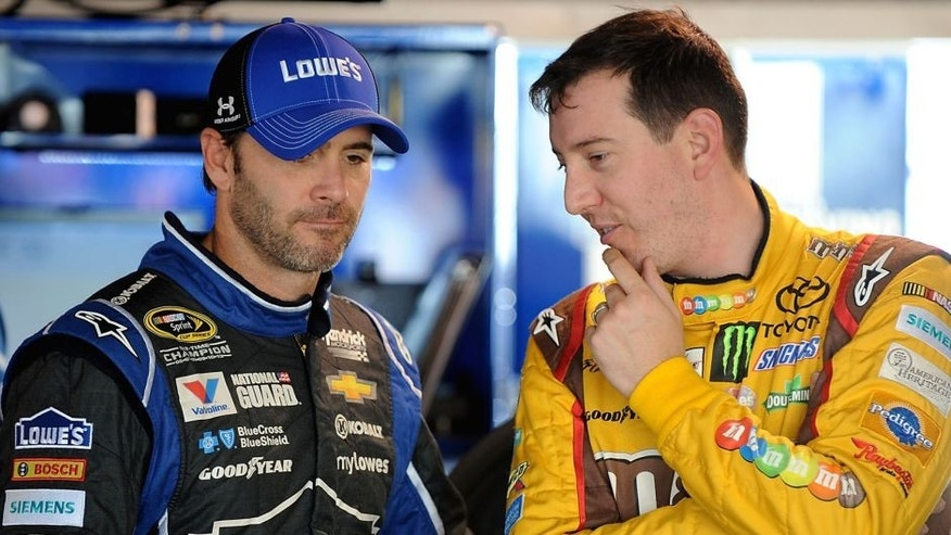 MARTINSVILLE, VA - OCTOBER 24: Jimmie Johnson, driver of the #48 Lowe's Chevrolet, left, and Kyle Busch, driver of the #18 M&M's Halloween Toyota, talk in the garage area during practice for the NASCAR Sprint Cup Series Goody's Headache Relief Shot 500 at Martinsville Speedway on October 24, 2014 in Martinsville, Virginia. (Photo by Jonathan Moore/Getty Images)