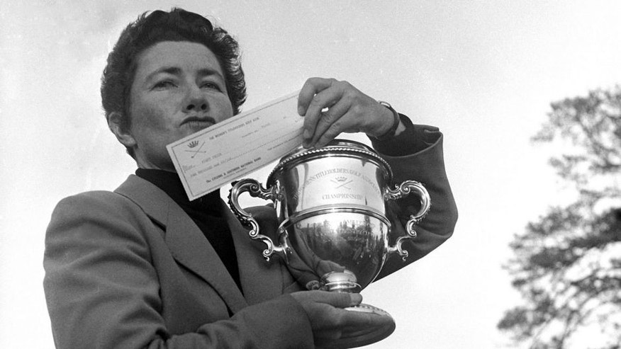 FILE - In this March 15, 1959 file photo, Louise Suggs of Atlanta, Ga., holds up the winner's cup and a check for $1,000 after winning the Women's Titleholders golf championship in Augusta, Ga. The LPGA Tour says Suggs, an LPGA founder and one of the greatest female golfers of all time, died Friday, Aug. 7, 2015, in Sarasota, Fla. She was 91. The LPGA did not list a cause of death. (AP Photo/Horace Cort, File)