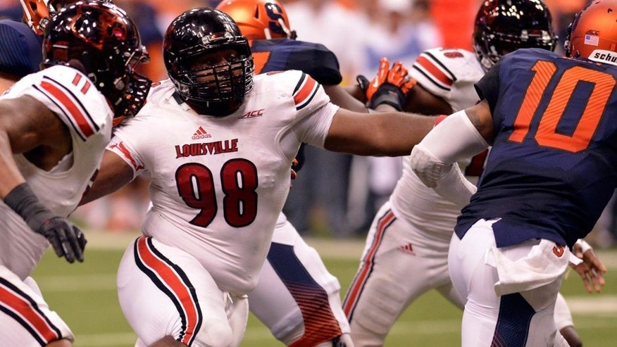 Oct 3, 2014; Syracuse, NY, USA; Louisville Cardinals defensive end Sheldon Rankins (98) chases Syracuse Orange quarterback Terrel Hunt (10) during the fourth quarter of a game at the Carrier Dome. Louisville won the game 28-6. Mandatory Credit: Mark Konezny-USA TODAY Sports
