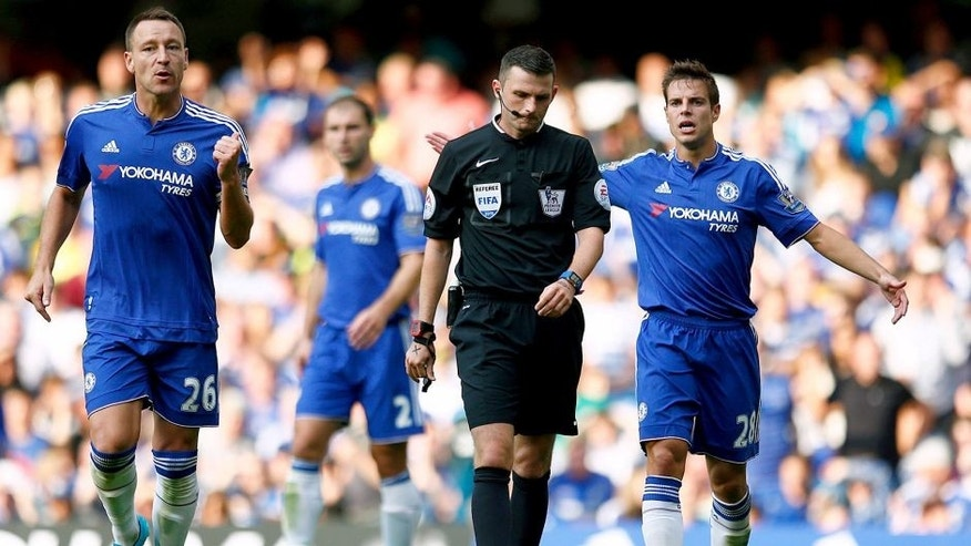 LONDON, ENGLAND - AUGUST 08: Referee Michael Oliver awards a penalty to Swansea after Thibaut Courtois of Chelsea bringing down Bafetimbi Gomis of Swansea City while Chelsea player appeal during the Barclays Premier League match between Chelsea and Swansea City at Stamford Bridge on August 8, 2015 in London, England. (Photo by Julian Finney/Getty Images)