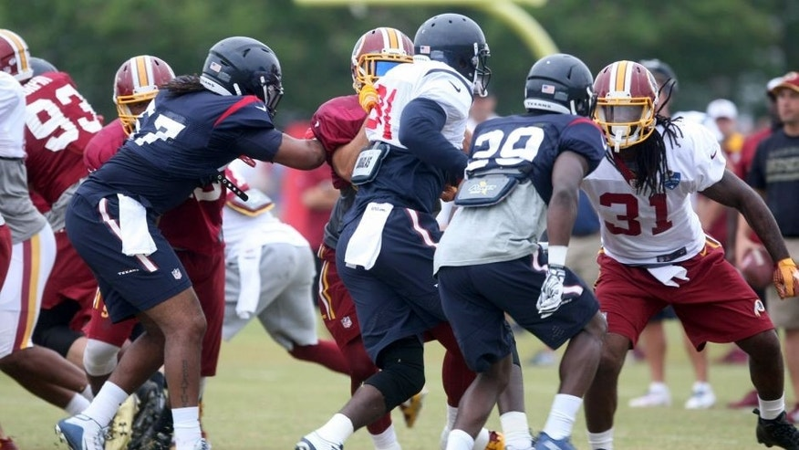 The Houston Texans defensive line practices against the Washington Redskins offensive line during a joint NFL training camp in Richmond, Va., Friday, Aug. 7, 2015. (AP Photo/Jason Hirschfeld)