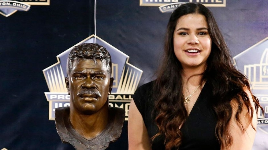 Sydney Seau, aughter of former NFL player Junior Seau, poses with a bust of her father during inductions at the Pro Football Hall of Fame Saturday, Aug. 8, 2015, in Canton, Ohio. (AP Photo/Gene J. Puskar)