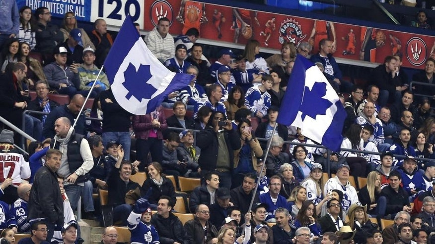 Jan 12, 2014; Toronto, Ontario, CAN; Fans wave Toronto Maple Leafs flags during a break in the action of the game against the New Jersey Devils at Air Canada Centre. The Maple Leafs beat the Devils 3-2. Mandatory Credit: Tom Szczerbowski-USA TODAY Sports