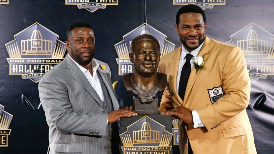 Aug. 8, 2015: Former NFL player Jerome Bettis, right, poses with his bust and with presenter and brother, John Bettis III, during inductions at the Pro Football Hall of Fame.