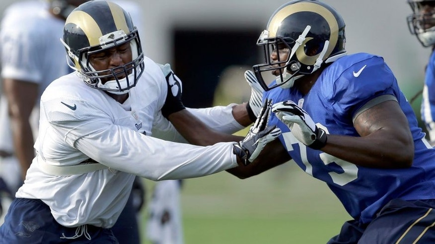 St. Louis Rams defensive end Robert Quinn, left, tries to get around tackle Greg Robinson during training camp at the NFL football team's practice facility Thursday, Aug. 6, 2015, in St. Louis. (AP Photo/Jeff Roberson)