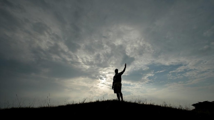 A course worker motions from a mound on the second hole during a practice round for the PGA Championship golf tournament at Whistling Straits Golf Course on Monday, Aug. 10, 2015 in Haven, Wis. (AP Photo/Chris Carlson)