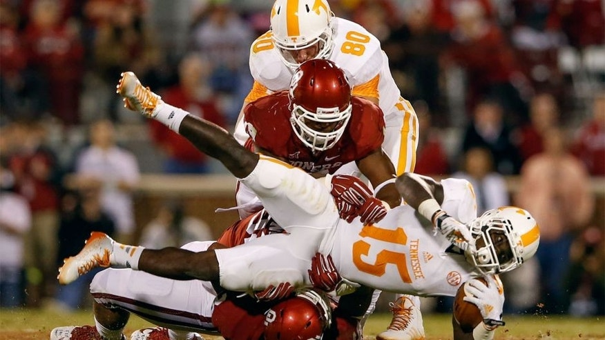 Sep 13, 2014; Norman, OK, USA; Tennessee Volunteers running back Marlin Lane (15) is tackled by Oklahoma Sooners linebacker Eric Striker (19) during the game at Gaylord Family - Oklahoma Memorial Stadium. Mandatory Credit: Kevin Jairaj-USA TODAY Sports