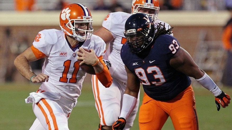 Nov 2, 2013; Charlottesville, VA, USA; Clemson Tigers quarterback Chad Kelly (11) runs with the ball past Virginia Cavaliers defensive tackle Donte Wilkins (93) to score a touchdown in the fourth quarter at Scott Stadium. The Tigers won 59-10. Mandatory Credit: Geoff Burke-USA TODAY Sports