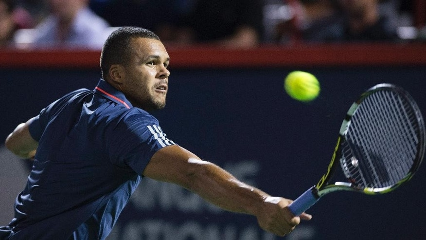 Jo-Wilfried Tsonga, of France, returns to Borna Coric, from Croatia, during their first round match at the Rogers Cup tennis tournament in Montreal on Monday, Aug. 10, 2015. (Graham Hughes/The Canadian Press via AP)