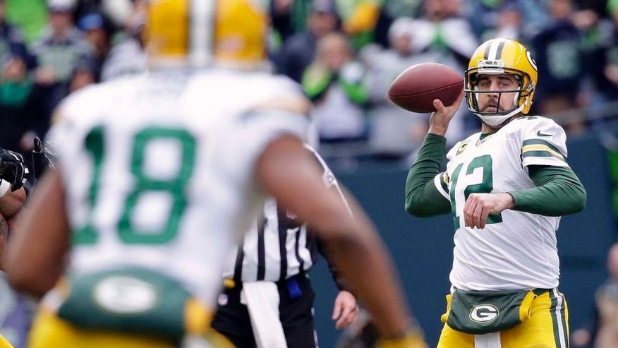 The Green Bay Packers' Aaron Rodgers (right) looks to pass to Randall Cobb during the first half of the NFC championship game in Seattle.