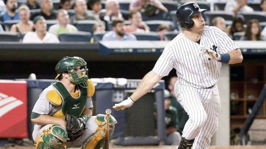 New York Yankees' Mark Teixeira, right, follows through on a solo home run as Oakland Athletics catcher Josh Phegley watches during the sixth inning of a baseball game, Wednesday, July 8, 2015, in New York. (AP Photo/Julie Jacobson)