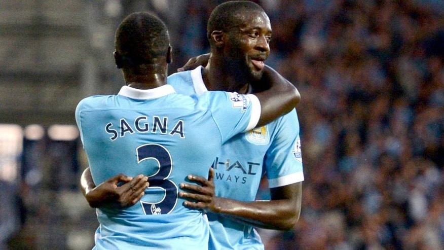 Manchester City's Ivorian midfielder Yaya Toure (R) celebrates with Manchester City's French defender Bacary Sagna after scoring his second goal during the English Premier League football match between West Bromwich Albion and Manchester City at The Hawthorns in West Bromwich, central England, on August 10, 2015. AFP PHOTO / OLI SCARFF RESTRICTED TO EDITORIAL USE. No use with unauthorized audio, video, data, fixture lists, club/league logos or 'live' services. Online in-match use limited to 75 images, no video emulation. No use in betting, games or single club/league/player publications. (Photo credit should read OLI SCARFF/AFP/Getty Images)