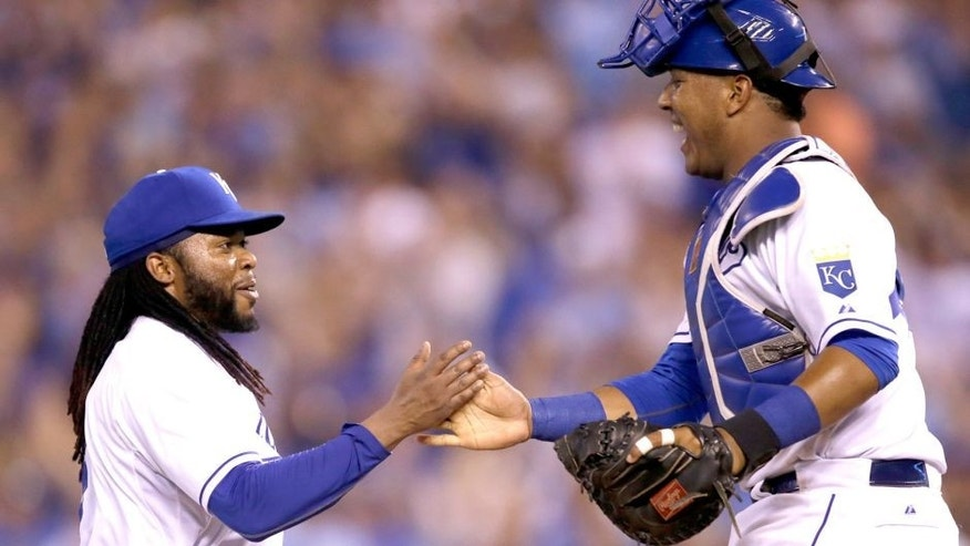 Kansas City Royals starting pitcher Johnny Cueto, left, is congratulated by catcher Salvador Perez, right, following a baseball game against the Detroit Tigers at Kauffman Stadium in Kansas City, Mo., Monday, Aug. 10, 2015. The Royals defeated the Tigers 4-0. (AP Photo/Orlin Wagner)