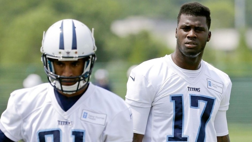Tennessee Titans wide receivers Dorial Green-Beckham (17) and Rico Richardson (81) watch teammates run a drill during an organized team activity at the team's NFL football training facility Monday, June 8, 2015, in Nashville, Tenn. An aggravated hamstring has limited Green-Beckham, who is working to reform his image after off-field issues dropped him into the second round of the draft. (AP Photo/Mark Humphrey)