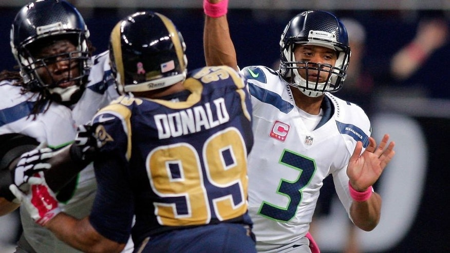 Oct 19, 2014; St. Louis, MO, USA; Seattle Seahawks quarterback Russell Wilson (3) throws a pass while under pressure from St. Louis Rams defensive tackle Aaron Donald (99) during the first half of a football game at the Edward Jones Dome. The Rams won 28-26. Mandatory Credit: Scott Kane-USA TODAY Sports