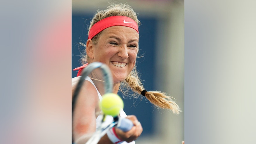 Victoria Azarenka, of Belarus, hits a return to Elina Svitolina, of Ukraine, at the Rogers Cup tennis tournament in Toronto, Tuesday Aug. 11, 2015.  (Frank Gunn/The Canadian Press via AP)
