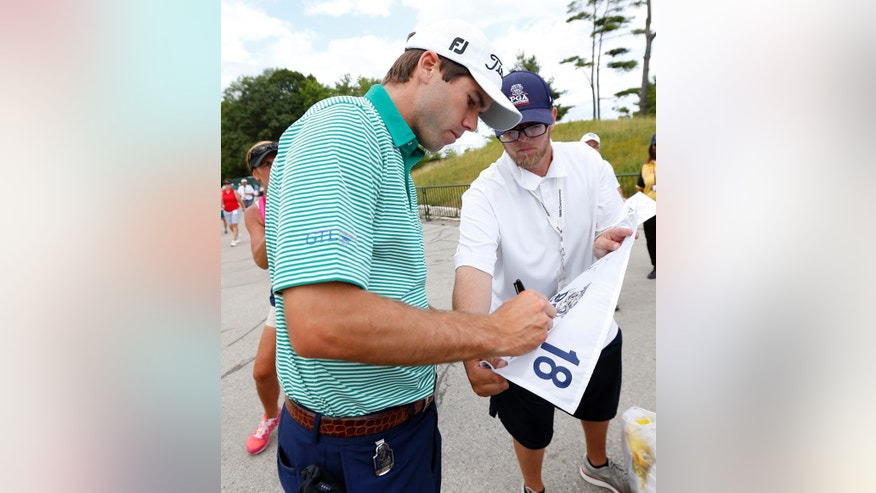 Ben Martin signs an autograph after a practice round for the PGA Championship golf tournament Tuesday, Aug. 11, 2015, at Whistling Straits in Haven, Wis. (AP Photo/Julio Cortez)