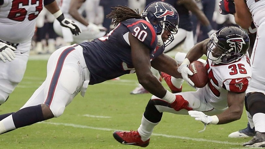 HOUSTON, TX- AUGUST 16: Jadeveon Clowney #90 of the Houston Texans stops Antone Smith #35 of the Atlanta Falcons for a loss in a pre-season NFL game on August 16, 2014 at NRG Stadium in Houston, Texas. (Photo by Thomas B. Shea/Getty Images)
