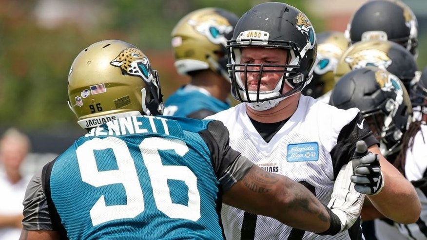 Jacksonville Jaguars tackle Josh Wells (72) blocks defensive tackle Michael Bennett (96) during a light scrimmage at NFL football training camp, Friday, July 31, 2015, in Jacksonville, Fla. (AP Photo/John Raoux)