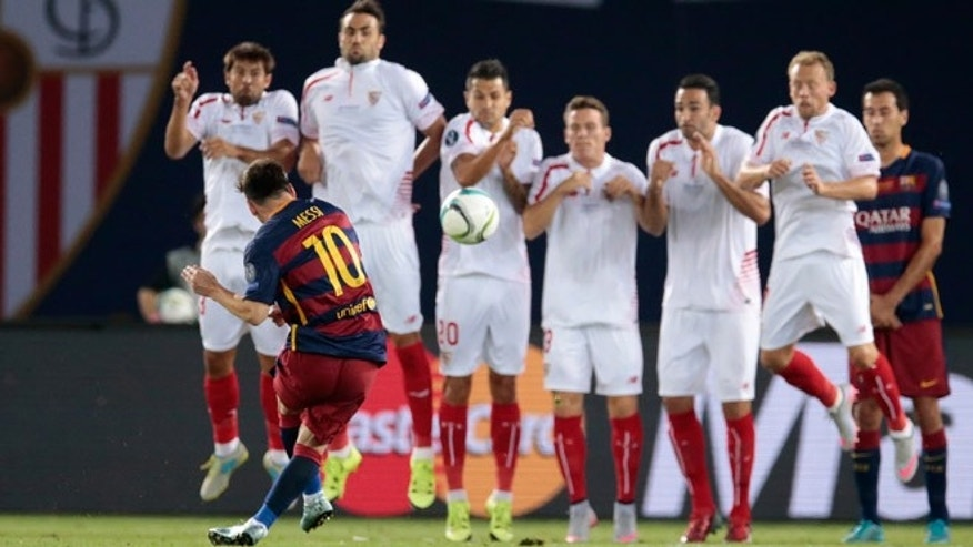 Barcelona's Lionel Messi, foreground, shoots a free kick to score his sideâs second goal during the UEFA Super Cup soccer match between FC Barcelona and Sevilla FC in Tbilisi, Georgia, on Wednesday, Aug. 12, 2015.
