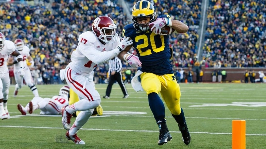 Nov 1, 2014; Ann Arbor, MI, USA; Michigan Wolverines running back Drake Johnson (20) duns the ball in for a touchdown Indiana Hoosiers cornerback Michael Hunter (17) attempts to tackle in the third quarter at Michigan Stadium. Mandatory Credit: Rick Osentoski-USA TODAY Sports