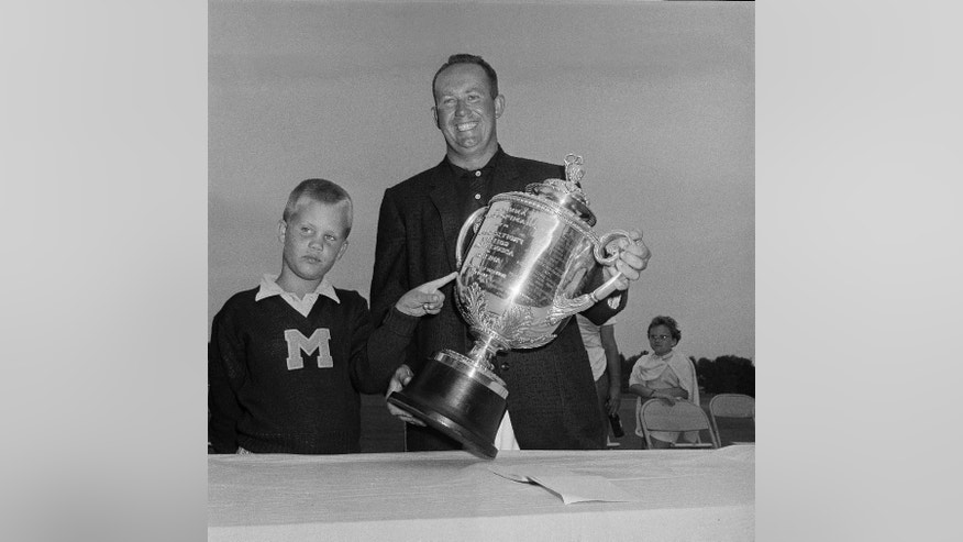 FILE - In this Aug. 2, 1959, file photo, Bob Rosburg Jr., points to the PGA Championship trophy held by his father, Bob Rosburg, after winning the golf tournament in Minneapolis. Rosburg is among the best five players to stage great comebacks in the PGA Championship. (AP Photo/Edward Kitch, File)