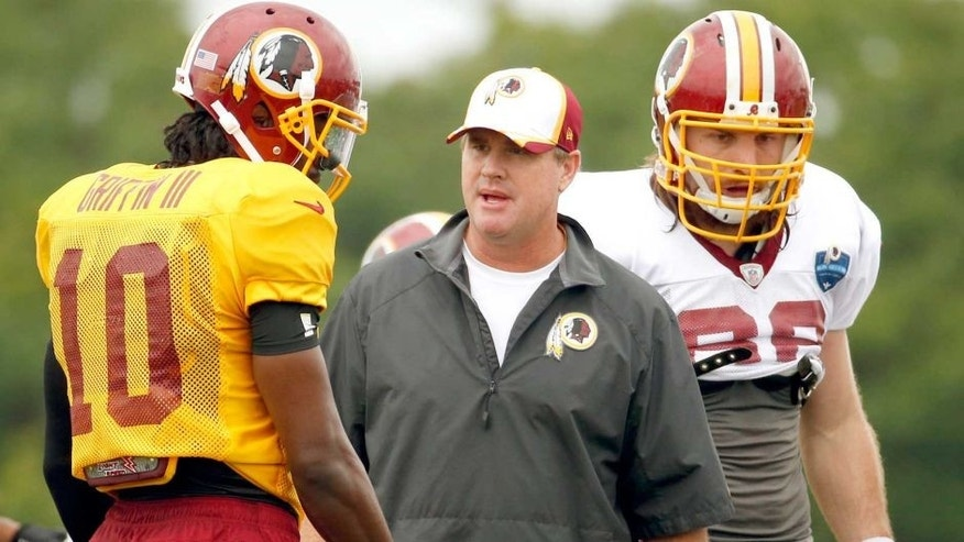 Washington Redskins head coach Jay Gruden, center, talks with quarterback Robert Griffin III, with tight end Logan Paulsen, right, during practice at the team's NFL football training facility, Sunday, July 27, 2014 in Richmond, Va. (AP Photo/Alex Brandon)