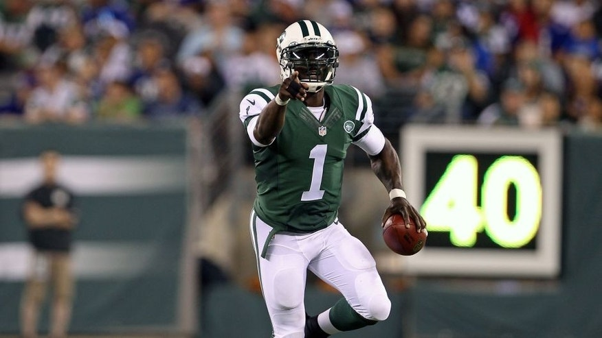 Aug 22, 2014; East Rutherford, NJ, USA; New York Jets quarterback Michael Vick (1) scrambles against the New York Giants during the second half at MetLife Stadium. The Giants defeated the Jets 35-24. Mandatory Credit: Adam Hunger-USA TODAY Sports