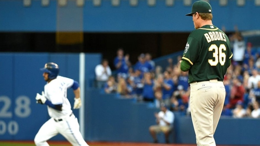 Aug 12, 2015; Toronto, Ontario, CAN; Oakland Athletics starting pitcher Aaron Brooks (36) watches Toronto Blue Jays designated hitter Chris Colabello (15) round the bases after hitting a three-run home run in the first inning at Rogers Centre. Mandatory Credit: Dan Hamilton-USA TODAY Sports
