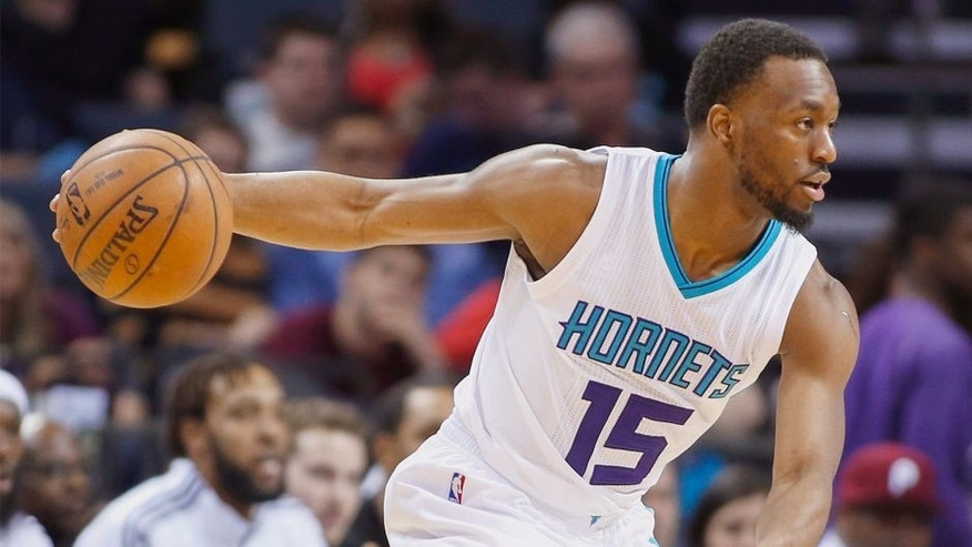 Charlotte Hornets guard Kemba Walker directs the offense against the Sacramento Kings during the second half of an NBA basketball game Wednesday, March 11, 2015 in Charlotte, N.C. Sacramento won 113-106. Walker returned to action after missing six weeks due to an injury (AP Photo/Nell Redmond)