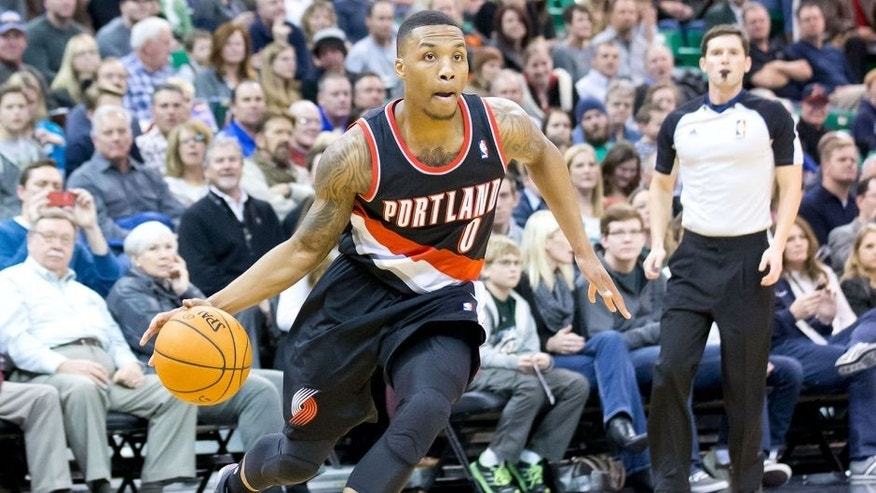 <p>Portland Trail Blazers point guard Damian Lillard (0) dribbles toward the basket during the first half against the Utah Jazz at EnergySolutions Arena. </p>