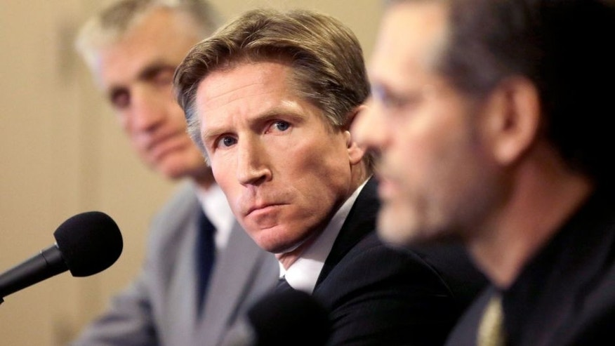 Philadelphia Flyers newly-hired head coach Dave Hakstol, center, and team president Paul Holmgren, left, look on as team general manager Ron Hextall, right, speaks during a news conference, Monday, May 18, 2015, in Philadelphia. (AP Photo/Matt Slocum)