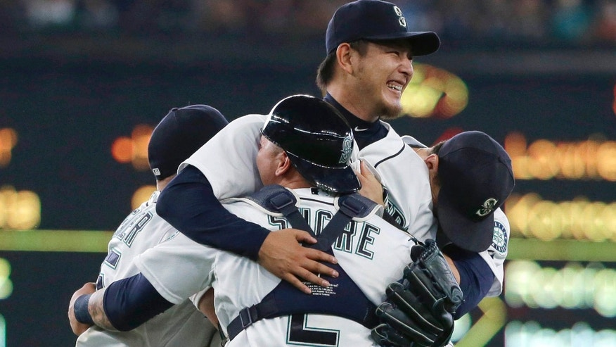 Aug. 12, 2015: Seattle Mariners starting pitcher Hisashi Iwakuma, center, is mobbed by teammates, including catcher Jesus Sucre (2), after Iwakuma threw a no-hitter against the Baltimore Orioles in a baseball game in Seattle.