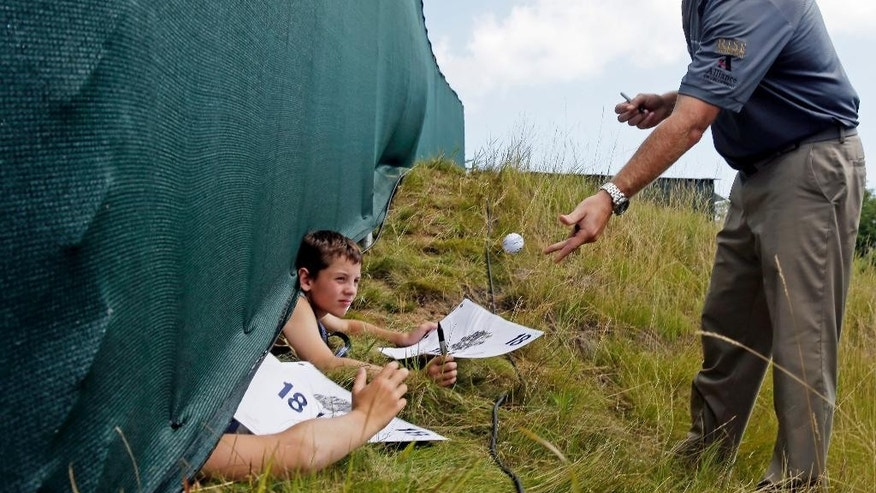 Ryan Helminen signs some autographs near the practice green during a practice round for the PGA Championship golf tournament Wednesday, Aug. 12, 2015, at Whistling Straits in Haven, Wis. (AP Photo/Chris Carlson)