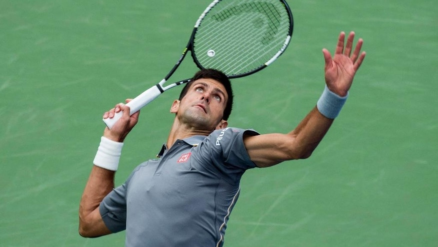 Novak Djokovic, of Serbia, reaches back to serve to Jack Sock, of the United States, during the Rogers Cup men's tennis tournament in Montreal, Thursday, Aug. 13, 2015. (Paul Chiasson/The Canadian Press via AP) MANDATORY CREDIT