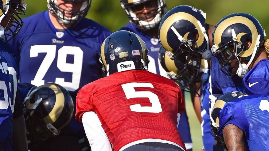 Aug 1, 2015; Earth City, MO, USA; St. Louis Rams quarterback Nick Foles (5) calls a play in a huddle at Rams Park. Mandatory Credit: Jasen Vinlove-USA TODAY Sports