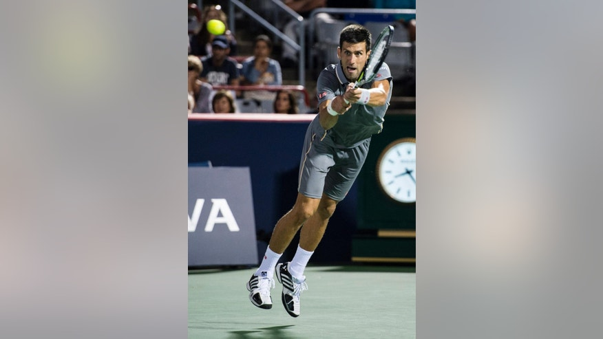 Novak Djokovic of Serbia returns to Ernests Gulbis of Latvia during the quarter finals at the Rogers Cup tennis tournament Friday Aug. 14, 2015 in Montreal. (Paul Chiasson/The Canadian Press via AP) MANDATORY CREDIT
