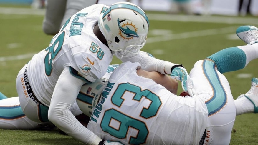 <p>Miami Dolphins outside linebacker Jason Trusnik (93) recovers a blocked punt as linebacker Chris McCain protects him during the first half of an NFL football game against the New England Patriots, Sunday, Sept. 7, 2014, in Miami Gardens, Fla. (AP Photo/Lynne Sladky)</p>