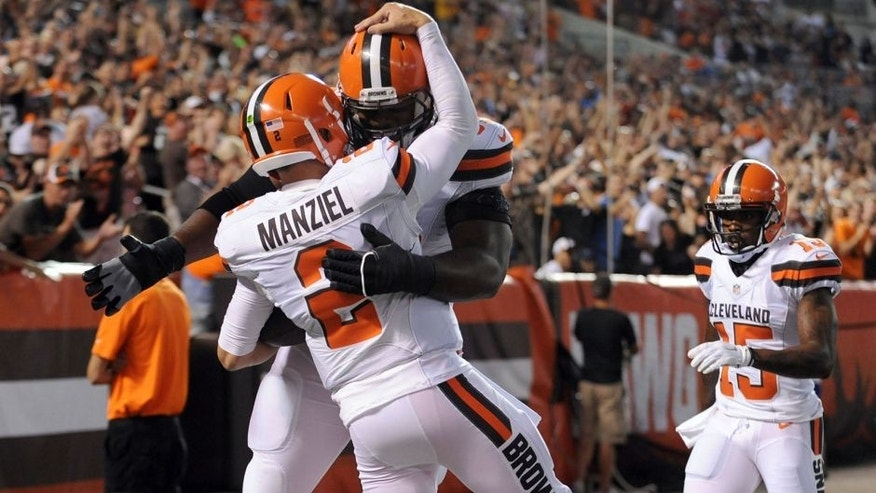Aug 13, 2015; Cleveland, OH, USA; Cleveland Browns quarterback Johnny Manziel (2) celebrates his touchdown run with Cleveland Browns guard Karim Barton (63) during the second quarter against the Washington Redskins in a preseason NFL football game at FirstEnergy Stadium. Mandatory Credit: Ken Blaze-USA TODAY Sports