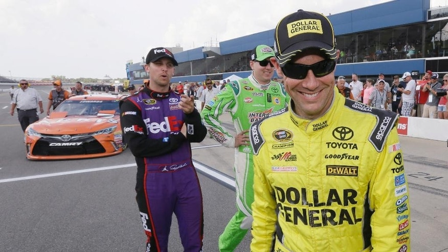Matt Kenseth, right, walks away after talking with Denny Hamlin, left, and Kyle Busch, center, after qualifying Friday, Aug. 14, 2015, for the pole position for the NASCAR Sprint Cup series auto race at Michigan International Speedway in Brooklyn, Mich. (AP Photo/Carlos Osorio)
