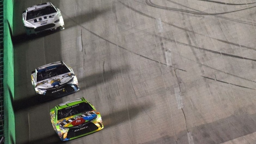 Kyle Busch, driver of the #18 M&M's Crispy Toyota, leads a pack of cars during the NASCAR Sprint Cup Series Quaker State 400 presented by Advance Auto Parts at Kentucky Speedway on July 11, 2015 in Sparta, Kentucky. (Photo by Jonathan Moore/Getty Images)