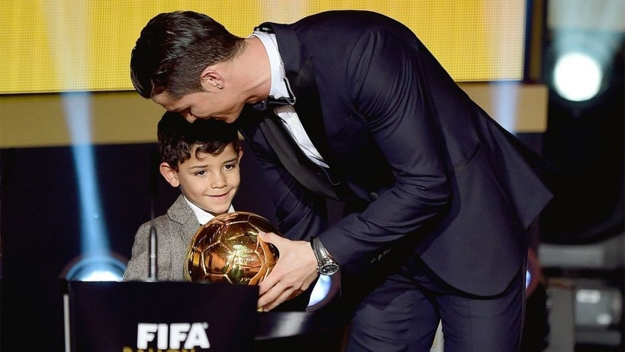 ZURICH, ENGLAND - JANUARY 12: FIFA Ballon d'Or winner Cristiano Ronaldo of Portugal and Real Madrid accepts his award with son Cristiano Ronaldo Junior during the FIFA Ballon d'Or Gala 2014 at the Kongresshaus on January 12, 2015 in Zurich, Switzerland. (Photo by Jamie McDonald - FIFA/FIFA via Getty Images)
