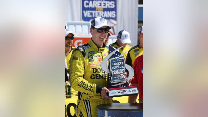 CORRECTS PHOTOGRAPHER'S BYLINE TO BOB BRODBECK INSTEAD OF DAVE FRECHETTE - Kyle Busch holds the trophy after winning the NASCAR Truck series Careers for Veterans 200 race at Michigan International Speedway, Saturday, Aug. 15, 2015, in Brooklyn, Mich. (AP Photo/Bob Brodbeck)