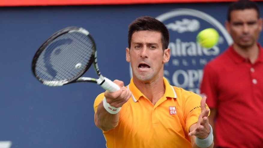 Novak Djokovic, of Serbia, hits a return to opponent Jeremy Chardy, of France, during the Rogers Cup semifinal tennis tournament, Saturday, Aug. 15, 2015 in Montreal.(Paul Chiasson/The Canadian Press via AP) MANDATORY CREDIT